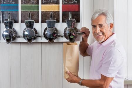Senior Man Buying Coffee Beans From Vending Machine photo