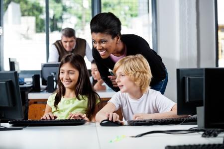 profesores: Maestro Feliz Ayudar a los escolares en Usar el ordenador Foto de archivo