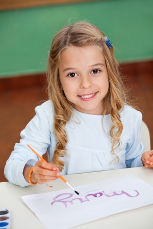 Girl Drawing At Desk In Kindergarten photo
