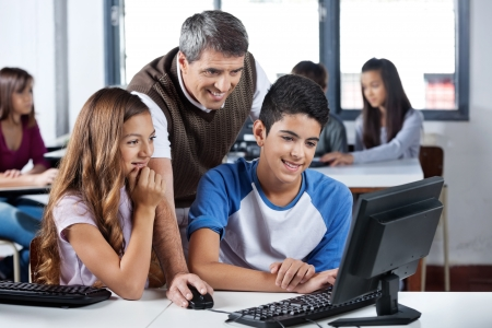 classroom: Happy Mature Teacher And Students Using Computer