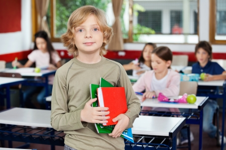 Schoolboy Holding Books While Standing In Classroom photo
