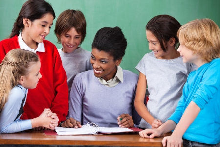 Happy Teacher Teaching Children At Desk In Classroom Stock Photo - 20591512