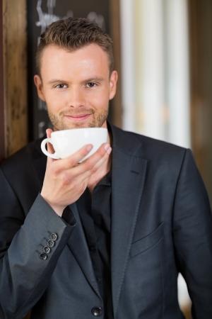 hombre tomando cafe: Confident Business Man Drinking Coffee Foto de archivo