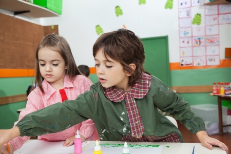 Boy With Girl Painting At Classroom Desk Stock Photo - 20592616