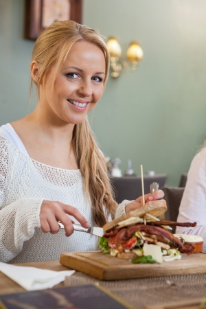 Young Woman Eating Sandwich In Restaurant photo