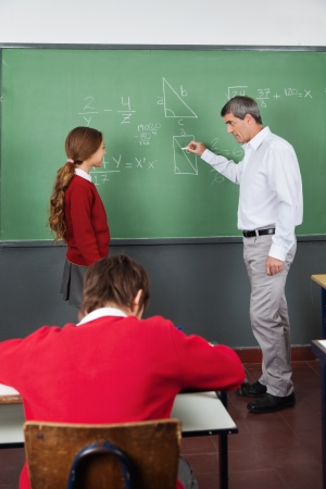 Male Teacher Teaching Geometry To Girl In Classroom photo