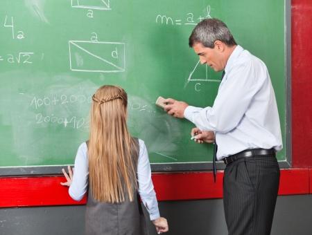 greenboard: Professor Teaching Mathematics To Little Girl On Board Stock Photo