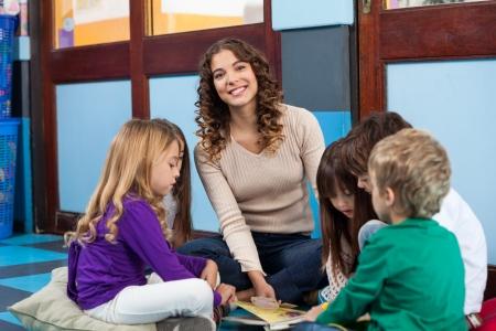legs crossed: Teacher With Children Reading Book In Classroom