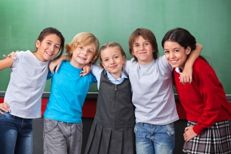 arms around: Cute Schoolchildren With Arms Around Standing Together In Classr Stock Photo