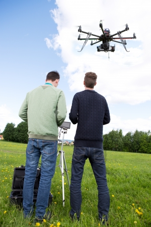 helicopter pilot: Photographer and Pilot Operate UAV