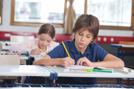 elementary school student: Little Boy Writing Notes With Classmate In Background