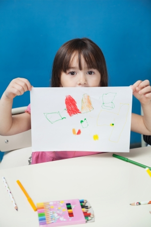 show case: Girl Showing Drawing Paper In Classroom Stock Photo