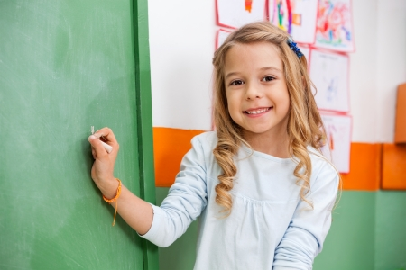 Cute Girl Writing On Board In Kindergarten photo