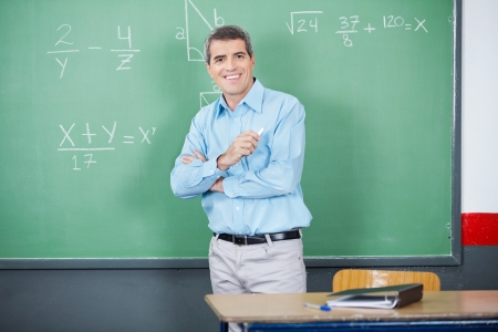 standing against: Male Teacher Standing Arms Crossed Against Board