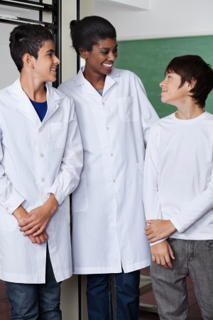 Teacher And Teenage Boys Standing Together In Science Lab photo