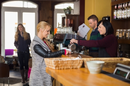 warm welcome: Female Bartender Serving Coffee To Woman