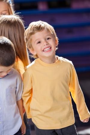 waistup: Boy Looking Away With Friends In Kindergarten