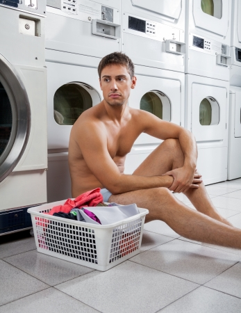 man laundry: Bored Man With Laundry Basket Waiting To Wash Clothes