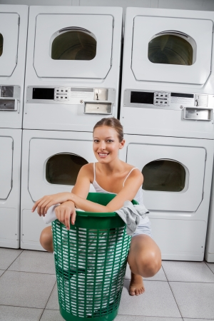 Woman With Clothes Basket In Laundromat photo
