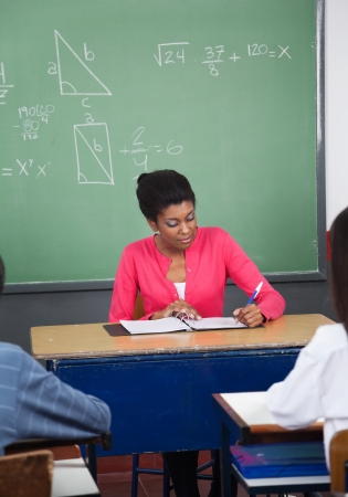 high school teacher: African American teacher writing in binder at desk with students in foreground