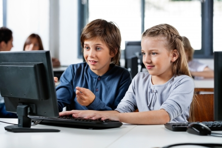 desktop computers: Boy Pointing While Using Desktop Pc With Friend At Desk Stock Photo