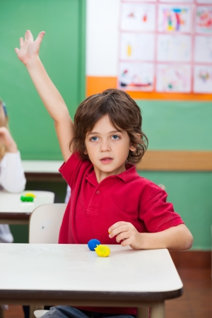 Boy With Hand Raised Sitting At Desk photo