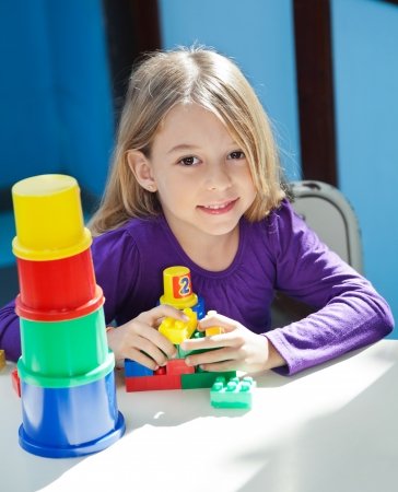 Girl Sitting With Toys At Desk In Preschool photo
