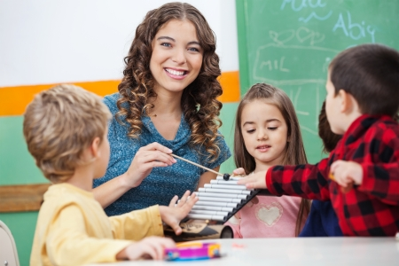 Teacher And Children Playing With Xylophone In Classroom photo