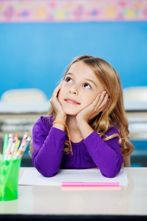 Girl Looking Up While Sitting With Head In Hands In Class