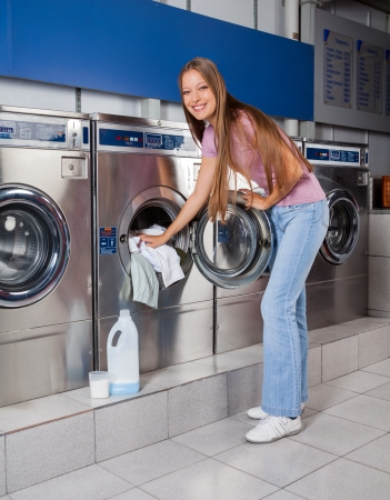 putting in: Woman Putting Clothes In Washing Machine
