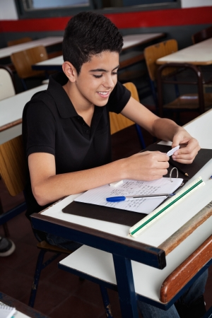 cheat: Schoolboy Copying From Cheat Sheet At Desk