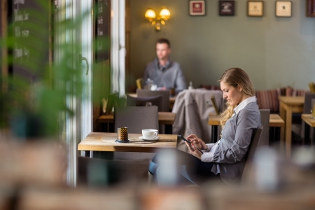 cafe shop: Side view of pregnant woman using digital tablet at cafe Stock Photo