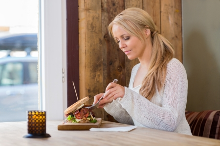 adult sandwich: Beautiful young woman eating burger at restaurant Stock Photo