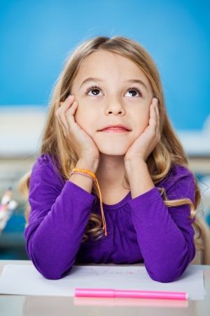Cute girl looking up while sitting with head in hands in drawing class Stock Photo