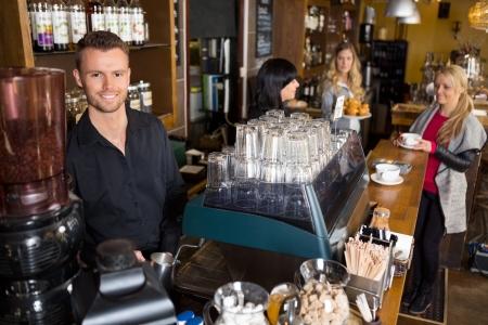Portret van mannelijke barman met collega werken op achtergrond in cafe Stockfoto