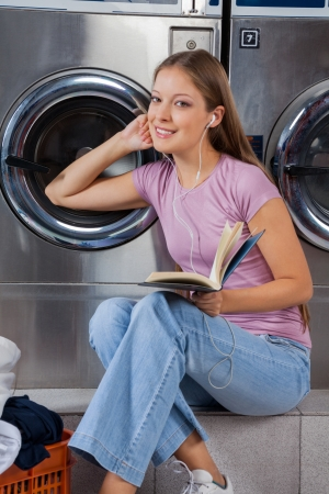 Woman With Book Listening To Music In Laundry photo