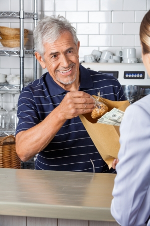 Salesman Giving Grocery Bag While Collecting Cash From Customer photo