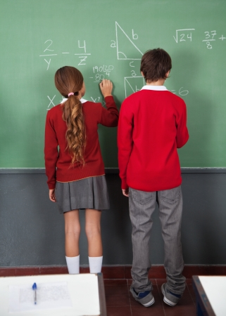 Teenage Schoolchildren Writing On Board photo