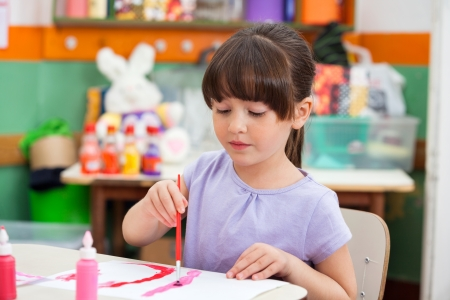 Girl Painting At Desk In Classroom photo