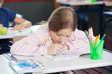 Schoolgirl Drawing In Book At Desk photo