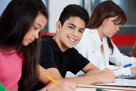 high school students: Schoolboy Sitting With Female Friends At Desk Stock Photo