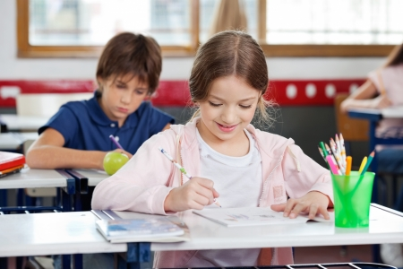 class room: Schoolgirl Smiling While Drawing In Classroom