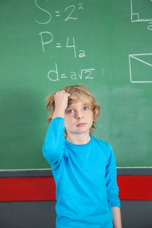 Sad Schoolboy Standing Against Board In Classroom photo