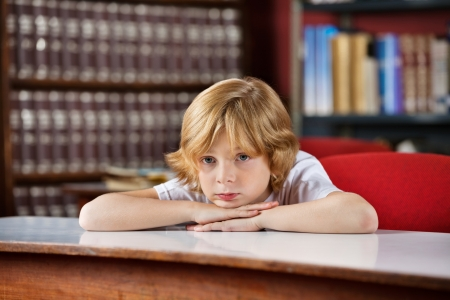 Bored Schoolboy Leaning On Table In Library photo