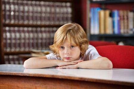 niños pensando: Colegial aburrido inclinada sobre la mesa en la biblioteca