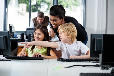 Teacher Assisting Boy Pointing On Computer In Lab Stock Photo - 20633449