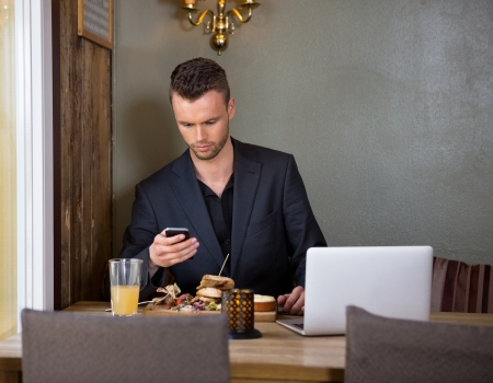 mobilephone: Businessman Messaging On Mobilephone While Having Meal In Cafe