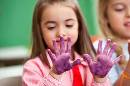 Girl Looking At Colored Hands In Art Class Stock Photo - 20633604