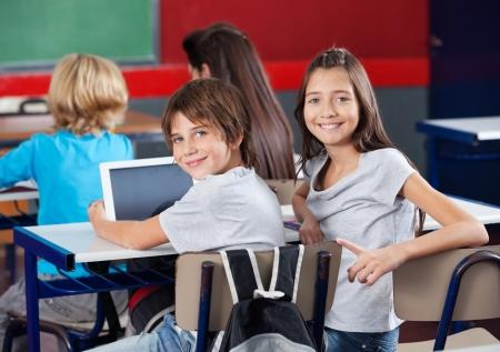Les écoliers avec tablette numérique assis en classe Banque d'images