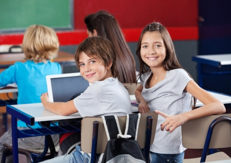 Los escolares con la tablilla digital que se sienta en el aula Foto de archivo - 20633613